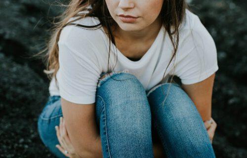 Unzufriedenheit - Brünette sitzt und umschlingt Beine