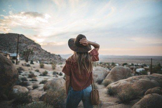 Innerer Frieden - Frau mit Hut steht in der Natur