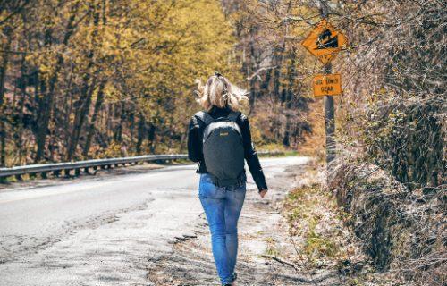 Blonde Frau von hinten läuft auf der Straße