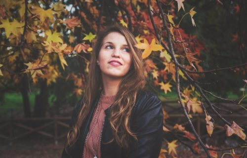 Selbstdisziplin - Frau schaut nach oben unter Herbstbaum