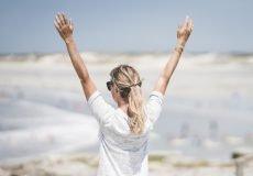 Willenskraft trainieren - Frau hält Arme hoch in die Luft