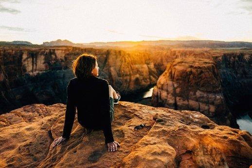 Mindset ändern - Frau sitzt auf einer Klippe beim Sonnenaufgang