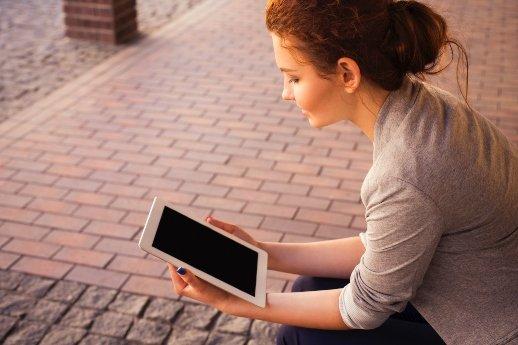 Mindset ändern - Frau sitzt mit dem Tablet in der Hand